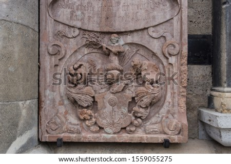 Relief sculpture on side of vintage gothic church with knight helmet and monk #1559055275