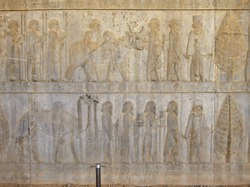 Reliefs depicting the Persian courtiers & guardians leading guests to their king. Guests & their servants are bringing gifts, such as bowls and animals, Persepolis, near Shiraz, Iran