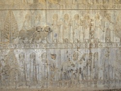 Reliefs from Apadana palace in Persepolis, ex-capital of Ancient Persia, near Shiraz, Iran. Bas-relief is depicting royal servants & nobles, bringing gifts to royal court