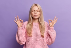 Relieved calm blonde woman searches peace inside makes mudra gesture reaches nirvana and breathes deeply with closed eyes isolated over purple background. Young female practices yoga indoor.