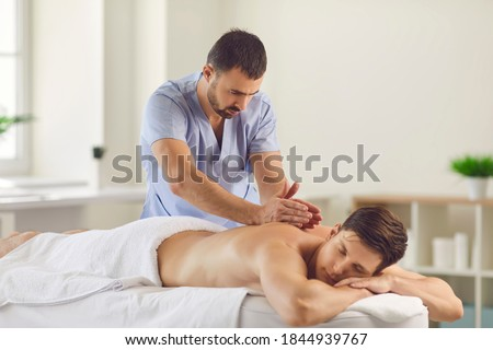 Relieving back muscle tension. Professional masseur massaging young man's back using Tapotement or chopping, tapping or hacking technique during Swedish massage therapy in spa salon or wellness center Foto stock ©