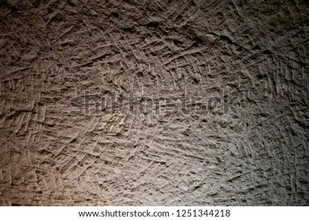 Relievo scratched surface of limestone wall in cave of Cappadocia Turkey. Natural limestone textured background. Grunge backdrop. Ancient wall in warm light with deep shadows. Rough stone texture.  #1251344218