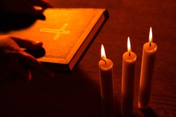 Religion and faith. Warm shot with a Bible and three burning candles. The direction of Christianity. Orthodoxy, Catholicism and Protestantism. Hands with a bible on the background of three candles.