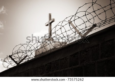 Religion and war concept - cross behind barbed wire