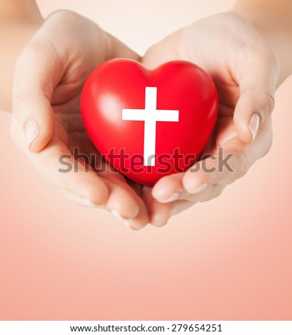 religion, christianity and charity concept - close up of female hands holding red heart with christian cross symbol over beige background #279654251