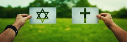 Religion conflicts as global issue concept. Two hands holding different faith symbols, Judaism vs Christianity belief over green field nature. Relations between different people doctrines and cult.