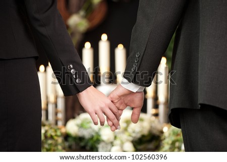 Religion, death and dolor  - couple at funeral holding hands consoling each other in view of the loss - stock photo