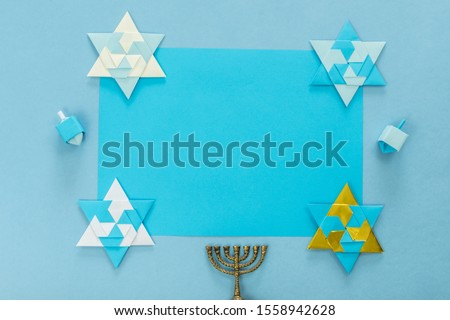 religion image of jewish holiday Hanukkah background with menorah (traditional candelabra), Spinning top and star origami, on blue table. top view. copy texts space. #1558942628