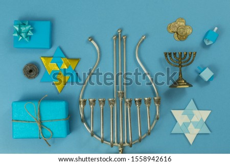 religion image of jewish holiday Hanukkah background with menorah (traditional candelabra), mud lamp, small gift, origami star, spinning top, coins, on blue table. top view. copy texts space. #1558942616