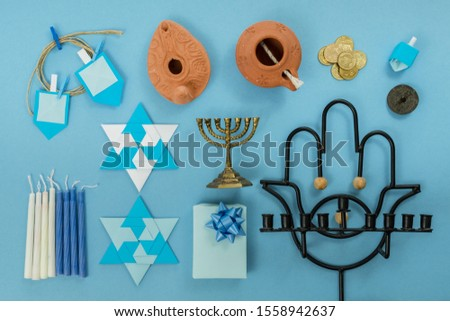 religion image of jewish holiday Hanukkah background with menorah (traditional candelabra), mud lamp, small gift, origami star, origami spinning top, coins, on blue table. top view. copy texts space. #1558942637