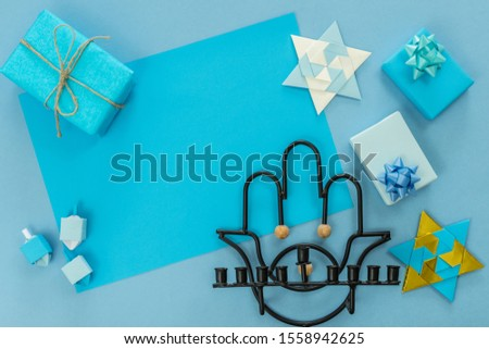 religion image of jewish holiday Hanukkah background with menorah (traditional candelabra), small gifts, origami spinning top and star, on blue table. top view. copy texts space. #1558942625