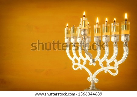 Religion image of jewish holiday Hanukkah with menorah (traditional candelabra) and oil candles over yellow background Stok fotoğraf ©