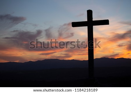 Religion theme, view of catholic cross in black shadow, with fantastic sunset with warm colors and mountains as background, in Viseu, Portugal