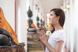 Religious Asian buddhist woman praying. Female buddhist disciple meditating, chanting mantra with prayer hand to the statue of lord Buddha in temple hall; asian young adult woman model
