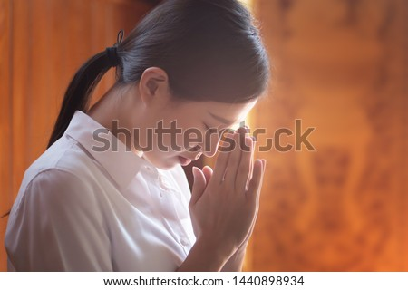 Religious Asian buddhist woman praying. Female buddhist disciple meditating, chanting mantra with prayer hand to the statue of lord Buddha in temple hall; Southeast Asian Dheravada Buddhism style