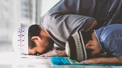 Religious Asian Muslim Man teaching his little son to pray to God in Sujud. The position involves having the forehead, nose, both hands, knees,all toes touch to ground.to praise and glorify Allah.