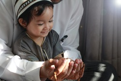 Religious Asian Muslim Man teaching his little son to pray to God with rosary at home.Sunset light shining through the window and touched boy body.Peaceful and Marvelous warm climate.Selective focus.