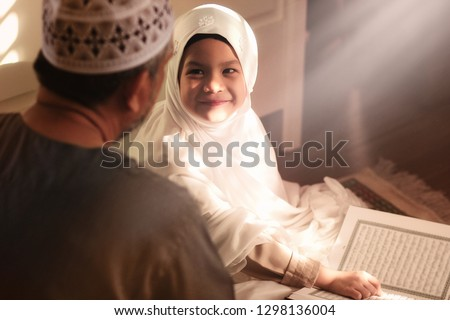 Religious Asian Muslim Man teaching his 6 years old daughter to learn the Quran and study Islam after pray to God at home .Sunset light shining through the window.Peaceful and Marvelous warm climate.