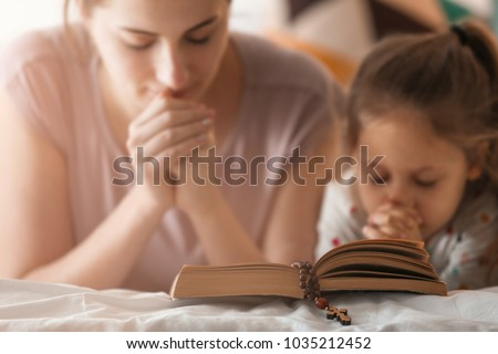 Religious Christian girl and her mother praying over Bible indoors #1035212452