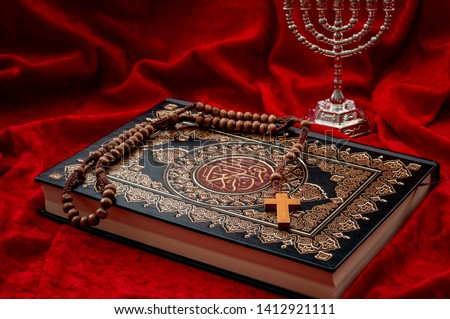 Religious coexistence, monotheism and abrahamic religions coexist in peace concept theme with a quran representing islam, a cross and rosary symbolizing christianity and menorah a symbol of judaism #1412921111