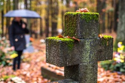 Religious cross in cemetery.  Mourning woman in black standing next to tombstone in rain.  Silent memory for dead relatives