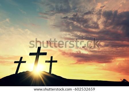 Religious cross silhouette against a bight sunrise sky #602532659