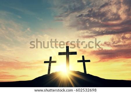 Religious cross silhouette against a bight sunrise sky #602532698