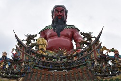 Religious giant red sculpture of Shennong (Wugushen), god of agriculture, sitting on traditional roof with asian art ornaments of taiwanese ancient Mazu Zhunan Wugu Xiandi Temple, Miaoli City, Taiwan.