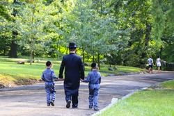 Religious Jew. A family of Hasidic Jews, a man with children, walks through the Autumn Park in Uman, Ukraine, Jewish New Year holiday
