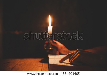 Religious man holding lit candles and reading the Holy Bible and praying in the Church, religion and faith concept #1334906405