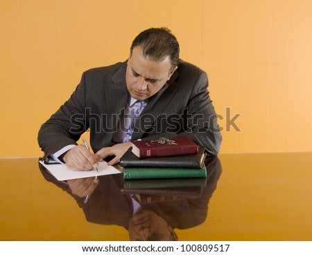 Religious man writing in his office with the Bible in front