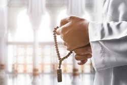 Religious muslim man praying with rosary beads