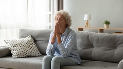 Religious older woman praying with hope, holding hands together in prayer, sitting on couch at home alone, thoughtful mature female with closed eyes meditating, feeling gratitude, making wish