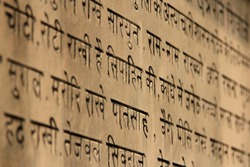 Religious scripture in Hindi on a stone temple wall