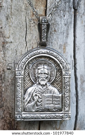 religious silver icon of Nikolai ugodnik (made in russia). Wood background.