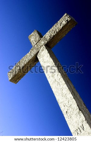 Religious stone cross on a beautiful blue sky
