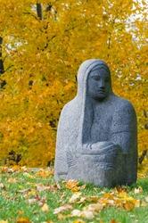 Religious stone figure of a woman against autumnal trees, Kumu art museum, Tallinn, Estonia