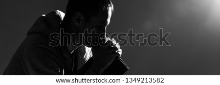Religious young man praying to God on dark background, black and white effect #1349213582