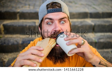 Relish the moment. Hipster drinking coffee with hotdog snack on stairs outdoor. Bearded man dining with unhealthy sandwich and beverage snack. Hungry guy enjoying snack on street. Snack and food.