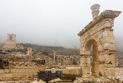 Remained honorific arched gate and Corinthian column at important Turkish archaeological site of Sagalassos on misty winter day