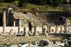 Remaining elements of State Agora columns with Corinthian capitals in ancient Greek city of Ephesus with Odeon ruins in background, Selcuk, Turkey