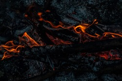 Remains from fire. Arson or natural disaster. Burning tree branches, hot red-orange coals from burnt wood. Bonfire background, close-up background, selective focus