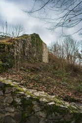 Remains of a castle wall under dramatic sky in winter.