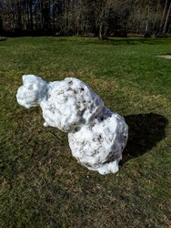 Remains of a melting snowman in early spring leaning to the side in sunlight ready to fall surrounded by green grass in early spring. Changing weather and seasons