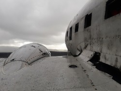 remains of a wing and part of the rusty cockpit of an old abandoned military plane on the coast of Iceland. In the background you can see a cloudy sky with gray gradients.