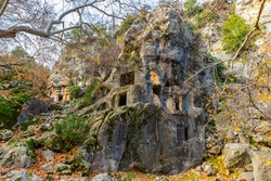 Remains of ancient Lycian rock hewn tombs in stone cliff in city of Pinara in Turkey