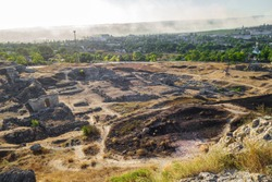 Remains of antique city Panticapaeum & modern city Kerch (Crimea) on background. Smoke above city makes a very dramatic feeling