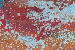 Remains of old paint on the concrete surface. Cracks in the wall, stones. Color - red, orange, blue.