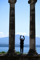 Remains of roman columns with silhouette of woman at Nyon  on a sunny summer afternoon with Lake Geneva ans French mountains in the background. Photo taken August 11th, 2021, Nyon, Switzerland.