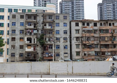 Remains of the last quarters with old residential buildings of workers, which will soon be destroyed and built up with skyscrapers in Sanya city, Hainan island, China. Selective focus